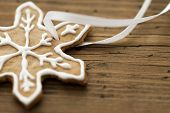 stock photo of ginger bread  - A Ginger Bread Star Cookie with white Decoration on Wood as Background with Copy Space - JPG