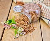 foto of buckwheat  - Buckwheat in a glass jar flower buckwheat napkin on the background of wooden boards - JPG