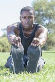 picture of hamstring  - Intense focused expression on muscular lean African American athlete holding toes of shoe while performing sitting hamstring stretch on grass lawn outside - JPG