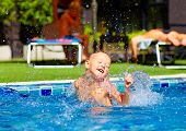 stock photo of exciting  - excited cute boy having fun in pool - JPG