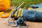 picture of pine-needle  - ball of threads knitting needles mittens and branch of pine on wooden background - JPG