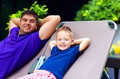 Father And Son Relaxing On Deckchair On Vacation