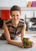Portrait Of Happy Young Housewife With Jar Of Pickled Cucumbers