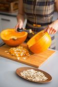 Closeup On Seeds And Young Housewife Removing Filling From Pumpk