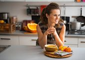 Young Housewife Eating Pumpkin Soup In Kitchen
