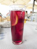 stock photo of sangria  - macro of crystal glass full of sangria typical spanish drink with slice lemon on white paper tablecloth restaurant - JPG