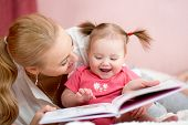 foto of nurture  - happy mother read a book to child girl indoors - JPG