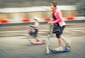 Young Woman And Child Riding On Scooters