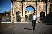 Stylish young man in front of Arco di Costantino, Rome, Italy