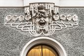 foto of building relief  - Head of a man among plants and seashells in a scream in bas - JPG