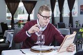 Businessman Reading At A Restaurant .