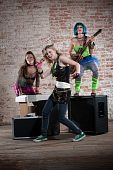 stock photo of groupies  - Young all girl punk rock band performs in front of brick wall - JPG