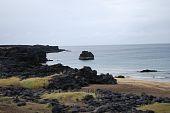 Golden beach amidst volcanic rock