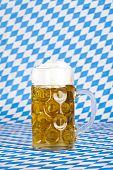 Oktoberfest beer stein and Bavarian flag in background.