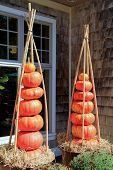 Two displays of stacked pumpkins outside home
