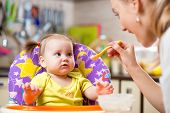 image of child feeding  - Happy mother spoon feeding child toddler indoors - JPG