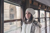 picture of tram  - Beautiful young woman wearing ecological fur poses on a tram - JPG