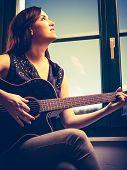 Beautiful Woman Playing Guitar By The Window