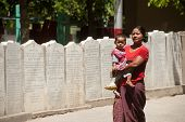Burmese Mother And Son Through The Ranks Of The Stone Slabs Of The Buddhist Canon (Tripitaka Texts).