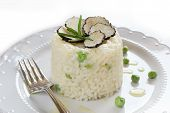 Italian Risotto With Black Truffle And Green Peas On White Plate