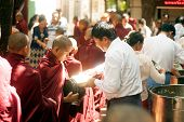 Peoples Giving With  Alms To A Buddhist Monk In Myanmar.