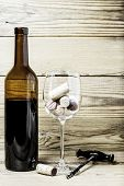 Wine glass, corks, corkscrew and bottle on a wooden background