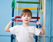 Strong child boy exercising with dumbbells