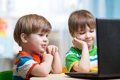 happy children looking at laptop