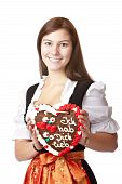 Woman in love dressed with Oktoberfest dirndl holding gingerbread heart.