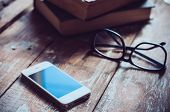 image of vintage antique book  - Old vintage books smartphone and glasses on a wooden table  - JPG