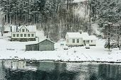 wooden houses on the banks of the Norwegian fjord, beautiful mountain landscape in winter