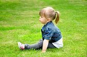 Cute little girl relaxing in green grass