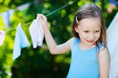 Adorable little girl having fun playing outdoors on summer day