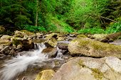 waterfall in the mountain forest. beautiful background of stone, water, moss.