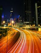 picture of skyscrapers  - Colorful city night scene with modern skyscrapers and cars motion blurred in Hong Kong - JPG