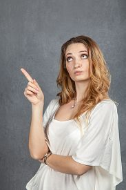 picture of disapproval  - Young woman showing disapproval with finger pointing in studio - JPG