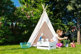 image of tipi  - Adorable little girl having fun playing outdoors on summer day - JPG