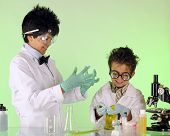 stock photo of mad scientist  - A preteen having fun with his preschool brother in a chemistry lab - JPG