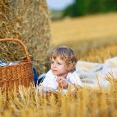 picture of natural blonde  - Cute blond kid boy having picnic on yellow hay field in summer outdoors - JPG