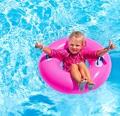 foto of one piece swimsuit  - Children sitting on inflatable ring in swimming pool - JPG