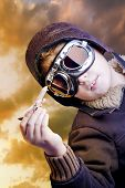 stock photo of bomber jacket  - Boy dressed up in pilot outfit at sunset sky - JPG