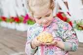 picture of eclairs  - Cute Little Girl Eating Eclair outdoors in the cafe - JPG