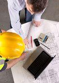 Two Men Discuss Building Plans