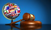 stock photo of human rights  - International law systems justice human rights and global business education concept with world flags on a school globe and a gavel on a desk on blue background - JPG