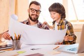 stock photo of blueprints  - Cheerful young man and his son looking through blueprint while sitting at working place - JPG