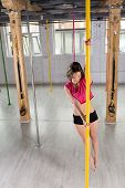 pic of pole dancer  - Sporty pole dancer training in fitness class - JPG