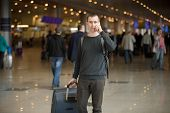 picture of people talking phone  - Portrait of young handsome man in 20s walking in modern airport terminal talking on smart phone travelling with luggage bag wearing casual style clothes blurred people on the background - JPG