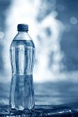 stock photo of bottle water  - PET bottle with water on a water surface background - JPG