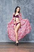 picture of swimsuit model  - Young and beautiful fashion model posing in studio in swimsuit and beach cape - JPG