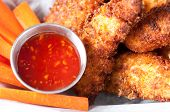 picture of strip  - chicken tenders or strips with a spicy chilli sauce and vegetable sticks - JPG